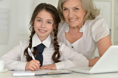 Little girl making homework with granny Stock Image