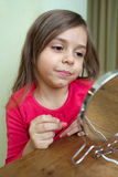 Applying lipstick. Little girl making makeup in front of small mirror Royalty Free Stock Photo