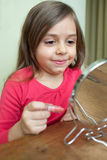 Applying lipstick. Little girl making makeup in front of small mirror Stock Photo