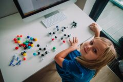Little girl making model of a molecule with computer program, learning chemistry, online learning and STEM