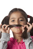 Little girl is making a moustache of her hair Stock Photos