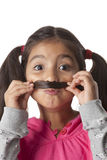 Little girl is making a moustache of her hair Royalty Free Stock Photography