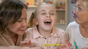 Little girl making moustache with pencil, having fun with parents, happiness stock footage