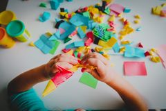 Little girl making origami crafts with paper. Learning stock photos