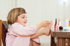 Little girl making pedicure stock images