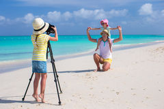 Little girl making photo of her dad and sister at the beach Royalty Free Stock Image