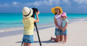 Little girl making photo of her mom and sister at Stock Photography