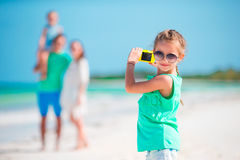 Little girl making photo on phone of family at the beach Stock Photography