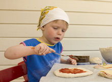 Little girl making pizza. Small child making a pizza Royalty Free Stock Images