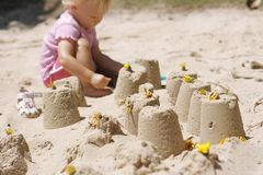 Little girl making sand castles Stock Photos
