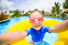 Little girl making selfie at inflatable rubber ring having fun in swimming pool Stock Photos