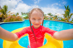Little girl making selfie at inflatable rubber ring in swimming pool Royalty Free Stock Photos