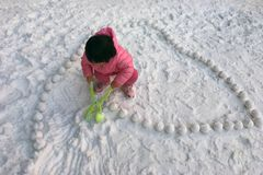 Little girl making snow ball royalty free stock images