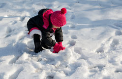 Little girl making a snowball Royalty Free Stock Image