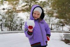 Little girl making snowballs Stock Photos