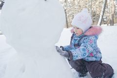 Little girl making snowman from natural snow Stock Image