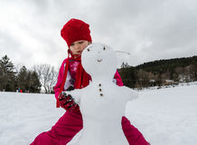 Little girl making snowman winter day Royalty Free Stock Photos