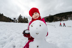 Little girl making snowman winter day Royalty Free Stock Photography