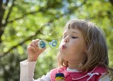 Little girl making soap bubbles Stock Photos