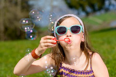 A little girl making soap bubbles Stock Photo