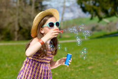A little girl making soap bubbles Stock Images