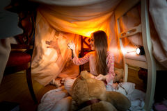 Little girl making theater of shadows in bedroom at night Royalty Free Stock Images