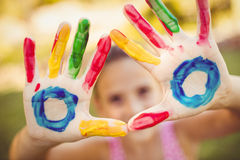 Little girl making a triangle with her painted hands to the camera Stock Image