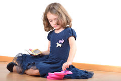 Little girl making up while wearing mother's shoes Royalty Free Stock Photography