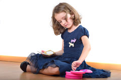 Little girl making up while wearing mother's shoes Royalty Free Stock Image