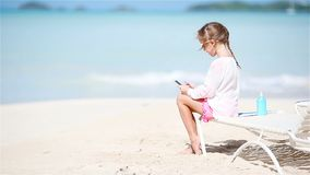 Little girl making video or photo with by her camera sitting on the sunbed. Adorable little girl with phone during summer vacation stock video footage