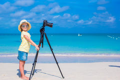 Little girl making video or photo with mobile phone. Little cute girl taking pictures on phone at tropical beach Royalty Free Stock Photo