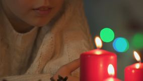 Little girl making wish for Christmas and blowing out candles, faith in miracle. Stock footage stock video footage
