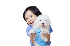 Little girl with Maltese dog on studio. Picture of a little girl playing with a Maltese dog while smiling at the camera in the studio Royalty Free Stock Photos