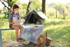 Little girl with map and book near tent outdoors. Summer camp stock photos