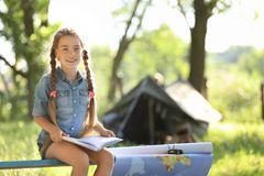 Little girl with map and book near tent outdoors. Summer camp stock image
