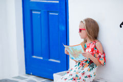 Little girl with map of island outdoors in old streets an Mykonos. Kid at street of typical greek traditional village Stock Photo
