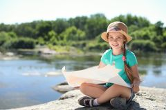 Little girl with map outdoors. Summer camp stock image
