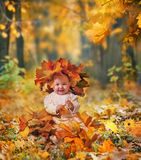 Little girl in maple leaves. Little girl playing with leaves in autumn park royalty free stock photo