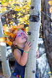 Little girl in maple leaves. Little girl playing with leaves in autumn park Stock Photos