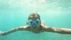 Little girl with mask exploring underwater in the Mediterranean Sea. A little girl with swimming mask exploring underwater in the Mediterranean Sea