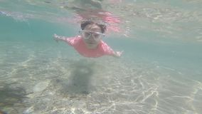 Little girl with mask swimming in the sea. Underwater footage. Slow motion stock video