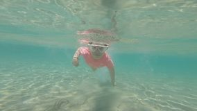 Little girl with mask swimming in the sea. Underwater footage. Slow motion stock footage
