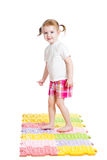 Little girl massaging her feet on mat. Little girl massaging her feet on carpet Stock Images