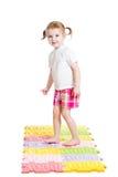 Little girl massaging her feet on mat Stock Images