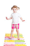 Little girl massaging her feet on mat Royalty Free Stock Photo