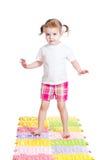 Little girl massaging her feet on mat Royalty Free Stock Photo