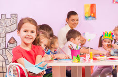 Little girl with mates in origami class. Group of kids and little girl on foreground show simple origami she made with other friends and nurse in class stock images