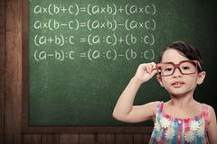 Little Girl With Math Formulas. Little schoolgirl with green chalkboard with math formulas Stock Image