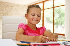 Little girl math homework. Cute young girl doing her math homework in school work book while sitting at living room table royalty free stock image