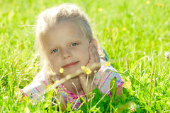 Little girl in the meadow. Little girl lying on grass royalty free stock photo